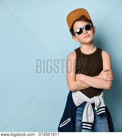 Stylish Kid In Sunglasses, Cap, Jeans, Black Shirt And Sports Jacket Around Waist Posing Seriously H