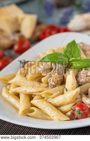 Penne Pasta In Creamy Sauce With Chicken, Tomatoes Decorated With Parsley