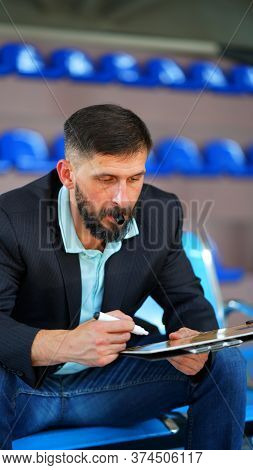 A Young Man Coach With Beard In Blazer On Bench In Basketball Court. Coach Drawing In A Coaching Tab