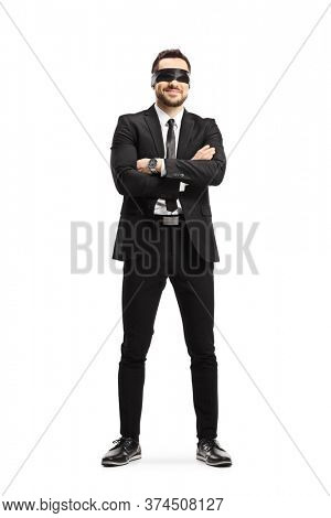 Full length portrait of a man in a black suit wearing a blindfold isolated on white background