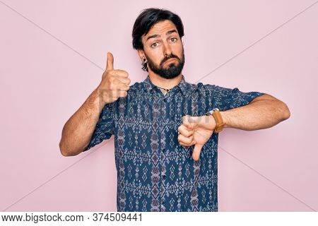 Young handsome hispanic bohemian man wearing hippie style over pink background Doing thumbs up and down, disagreement and agreement expression. Crazy conflict