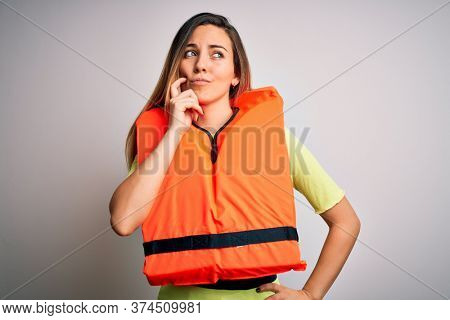 Young beautiful blonde woman with blue eyes wearing orange lifejacket over white background with hand on chin thinking about question, pensive expression. Smiling with thoughtful face. Doubt concept.