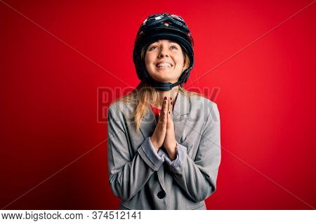 Young beautiful blonde motorcyclist woman wearing motorcycle helmet over red background begging and praying with hands together with hope expression on face very emotional and worried. Begging.