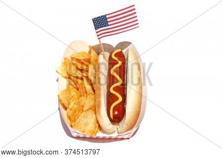 Hot Dog. Hot Dog with Mustard, Potato Chips and an American Flag. Isolated on white. Room for text. Hot Dogs are a perfect meal for any Holiday Lunch. 4th of July Hot Dog and Potato Chips with Flag.