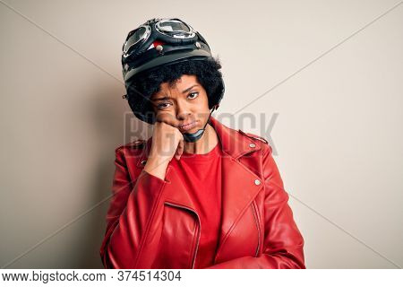 Young African American afro motorcyclist woman with curly hair wearing motorcycle helmet thinking looking tired and bored with depression problems with crossed arms.