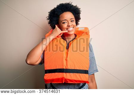 Young African American afro woman with curly hair wearing orange protection lifejacket smiling doing phone gesture with hand and fingers like talking on the telephone. Communicating concepts.