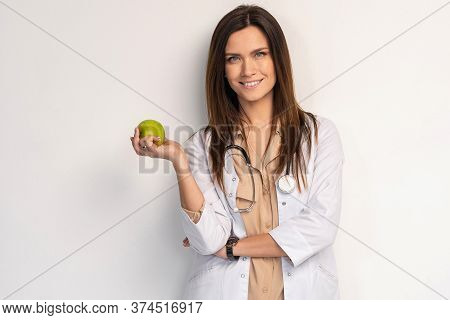 Medical Doctor Woman Smile With Stethoscope Hold Dreen Fresh Apple In Hand. Isolated Over White Back