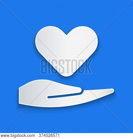 Paper Cut Heart On Hand Icon Isolated On Blue Background. Hand Giving Love Symbol. Valentines Day Sy
