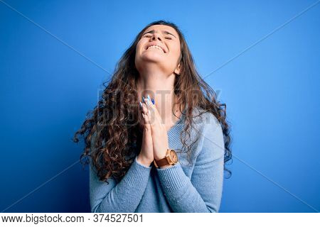 Young beautiful woman with curly hair wearing blue casual sweater over isolated background begging and praying with hands together with hope expression on face very emotional and worried. Begging.