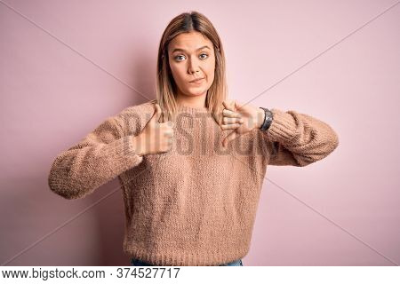 Young beautiful blonde woman wearing winter wool sweater over pink isolated background Doing thumbs up and down, disagreement and agreement expression. Crazy conflict