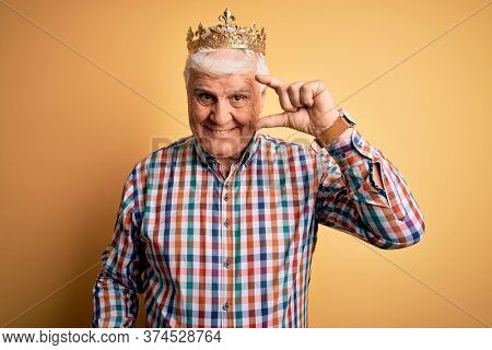 Senior handsome hoary man wearing golden crown of king over isolated yellow background smiling and confident gesturing with hand doing small size sign with fingers looking and the camera. Measure.