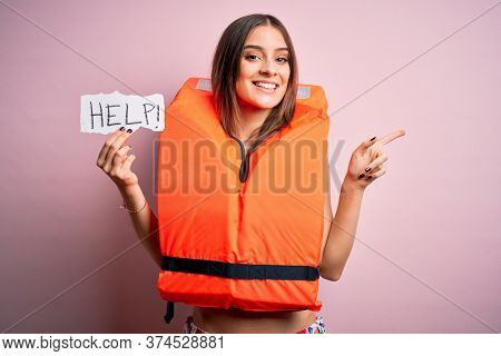 Young beautiful brunette woman wearing lifejacket holding paper with help word message very happy pointing with hand and finger to the side