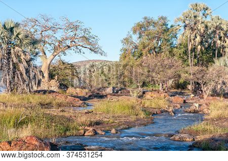 Epupa, Namibia - May 24, 2011: A Woman Washing A Child In The Kunene River At The Top Of The Epupa W