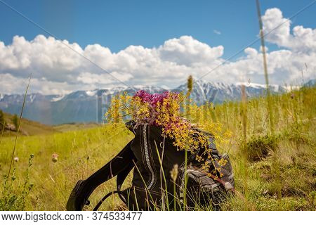 Backpack With A Bouquet Of Flowers During A Halt In The Mountains.