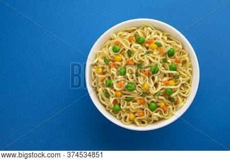 Bowl Of Instant Noodles Isolated On Blue Background, Top View