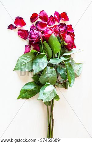 Bouquet Of Withered Red Rose Flowers And Fallen Petals On Pale Brown Table