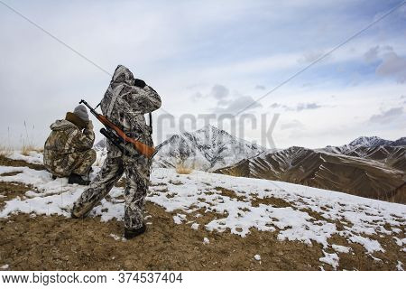 Hunters In The Mountains In Winter Camouflage Watching Through Binoculars. Two Hunters In Light Camo