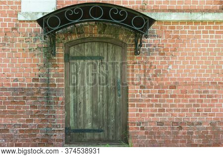 A Close-up Of An Old Wooden Door With Wrought-iron Loops And An Iron Visor Against The Background Of