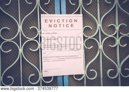 Foreclosed Or Eviction Notice On A Main Door With Blurred Details Of A House With Vintage Filter.
