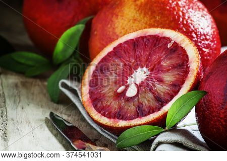 Cut Sicilian Bloody Oranges On A Gray Cloth And A Knife On An Old Wooden Table In Rustic Style, Sele