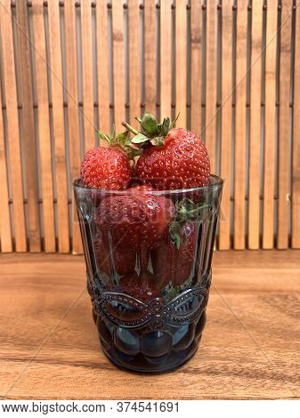 Strawberries On A Wooden Tray. Wooden Table, Background. Red Strawberries, Blue Glass Cup.