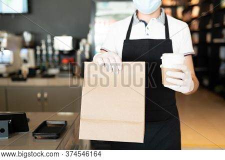 Midsection Of Male Staff Holding Parcel And Disposable Coffee Cup At Takeout Counter In Cafe