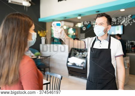 Male Employee Checking Body Temperature Of Young Woman Through Thermal Scanner In Restaurant