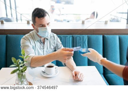 Mid Adult Man In Face Mask Making Payment Through Credit Card At Coffee Shop