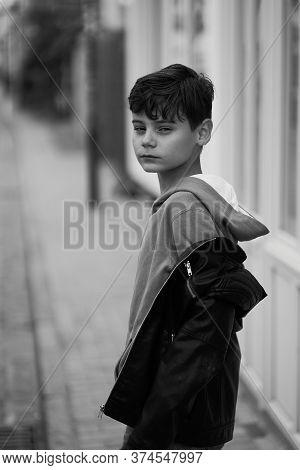 Teenager Boy In Hoodie And Leather Jacket Walks Away On The City Street And Turns Around. Black And