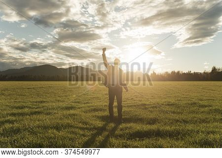 Businessman In A Suit Standing With His Arm Raised In Triumph In The Middle Of Beautiful Green Meado