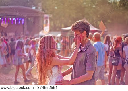 Couple In Paint And Powder At Holi Paint Festival. A Girl And A Guy Sprinkle Each Other With Paints.