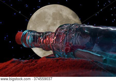 A Closeup Low Angle Shot Of A Message In A Bottle Revealed In The Sandy Shoreline During The Night T
