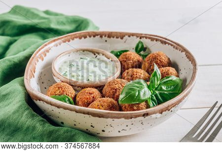 Bowl Of Falafel With Tzatziki Sauce On A White Wooden Table. Selective Focus