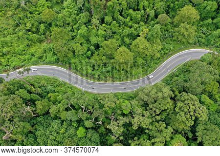Scenic road through forest with traffic driving. Aerial drone view of route through rainforest jungle