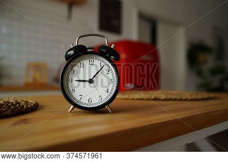 Close Up Of Alarm Clock On Table In Kitchen. Black Vintage Clock On Kitchen Table.