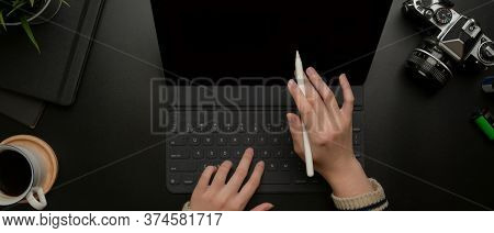 Hands Using Digital Tablet With Stylus On Dark Modern Office Desk With Camera And Supplies