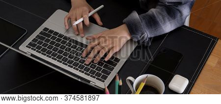 Hands Typing On Laptop Keyboard On Modern Office Desk With Smartphone, Stationery And Coffee Cup