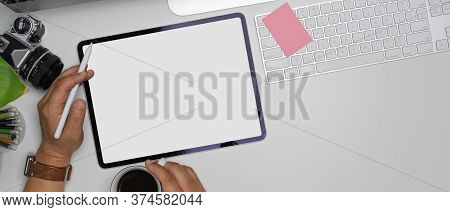 Male Left Hand Using Mock-up Tablet While Right Hand Holding Coffee Cup On White Office Desk