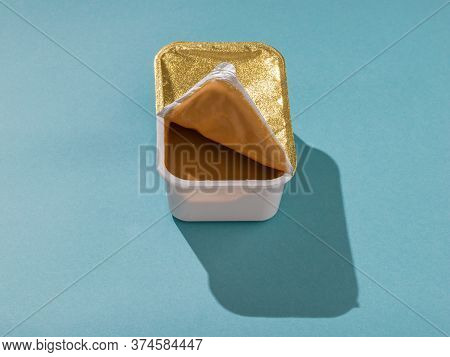 A Container Of Peanut Paste On A Light Blue Table In A Bright Light. Natural Peanut Cream.