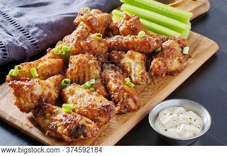pile of bbq garlic bone-in chicken wings on wooden board