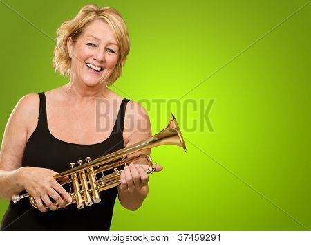 Happy Mature Woman Holding Trumpet On Green Background poster