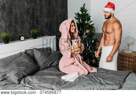 A Man Makes A New Year's Gift To His Woman. A Loving Couple Enjoys The New Year Holiday And Give Eac