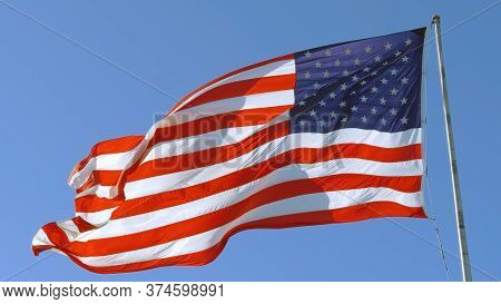 American Flag On A Blue Sky Background. Usa Flag Flaping In Wind. Close-up Of An American Flag Flyin