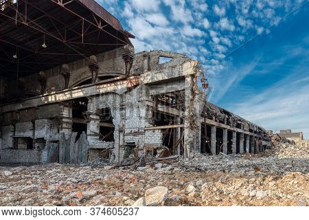 Old Abandoned Factory Building. The Walls And Roof Of The Building Are Partially Destroyed.