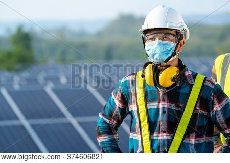 Electrician With Engineer Wearing A Medicine Healthcare Mask Working And Checking At Solar Power Sta