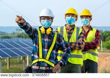 Solar Power Plant,electrician Wearing A Medicine Healthcare Mask Working And Checking Solar Plant At