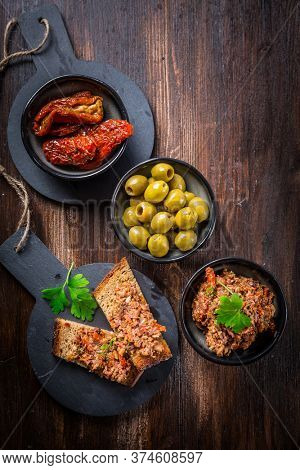 Tapenade - delicious olive paste from France with ingredients and crostini. Top view.