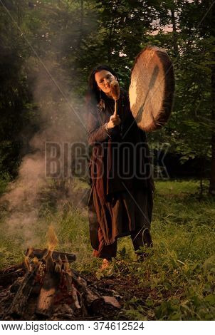 Shaman Woman Playing On Shaman Frame Drum Near Large Fire In Forest At Dusk