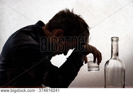 A Silhouetted Photo. A Man In Alcoholic Intoxication Holds A Glass Of Alcohol. Alcoholism, Addiction