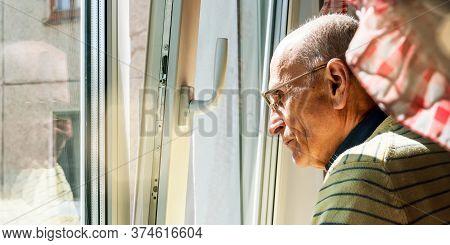 Senior Man In Yellow Pullover And Glasses Stands Near White Plastic Window Under Bright Summer Morni